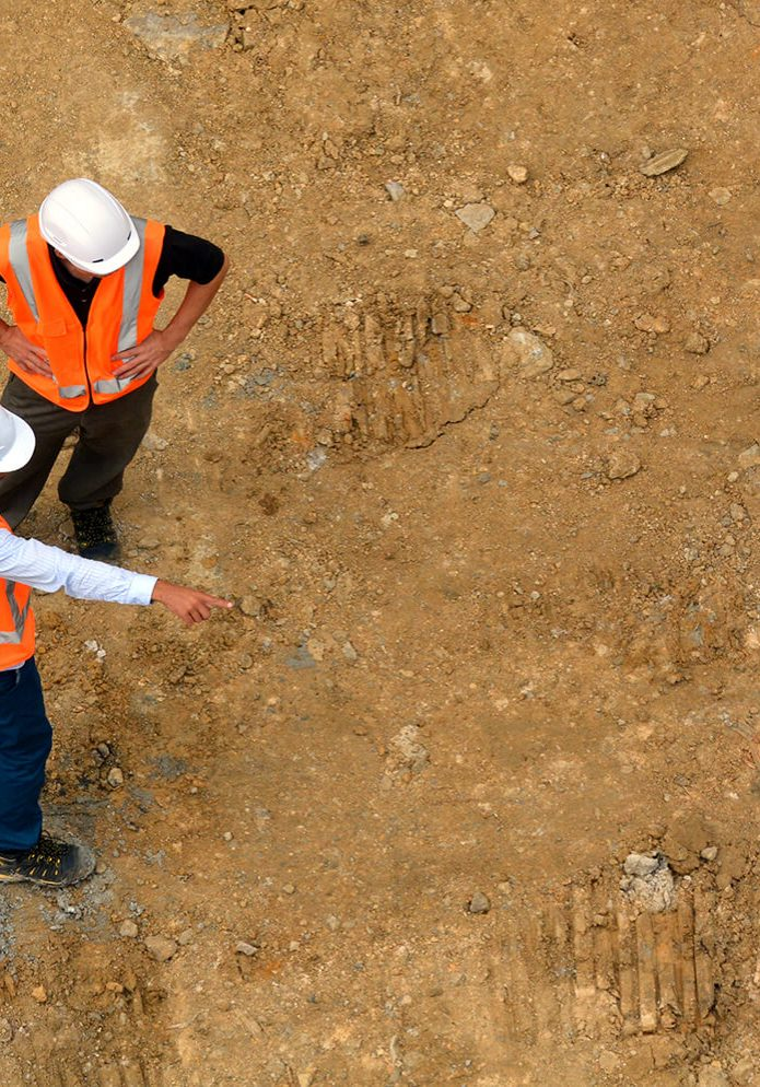 stock-photo-aerial-view-of-two-unrecognized-civil-engineers-inspecting-construction-site-building-development-393147385